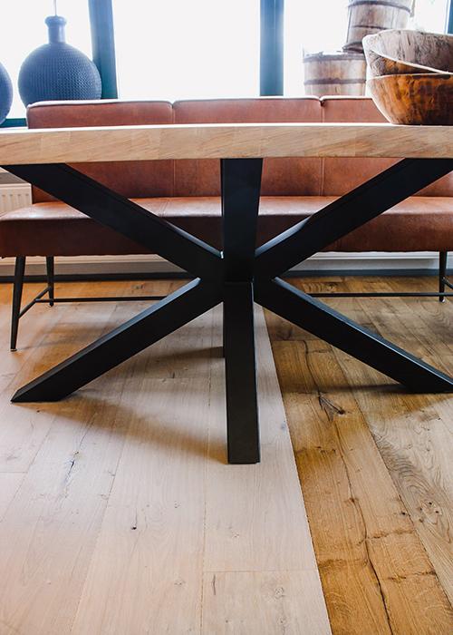 Metalen kruispoot in het midden onder tafel